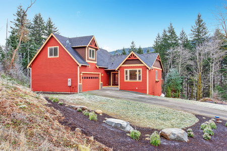 Red clapboard siding house. View of garage with drive way and entrance porch photo