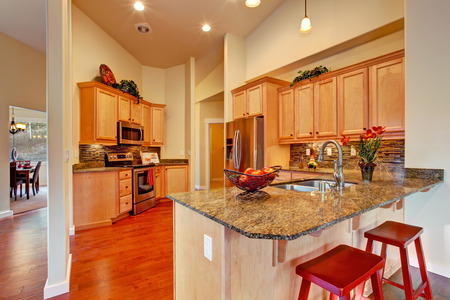 back kitchen: Soft colors modern kitchen area with wooden storage cabinets, steel appliances and tile back splash trim
