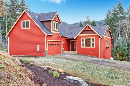 Red clapboard siding house  View of garage with drive way and entrance porch photo