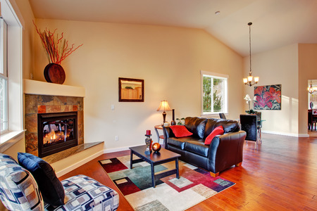 fireplace living room: Cozy living room interior with fireplace, black leather couch and dining area