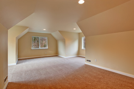 vaulted: Empty room with vaulted ceiling, carpet floor and windows Stock Photo