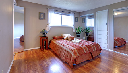 Simple yet comfortable bedroom with mirror doors closets, hardwood floor and small window photo
