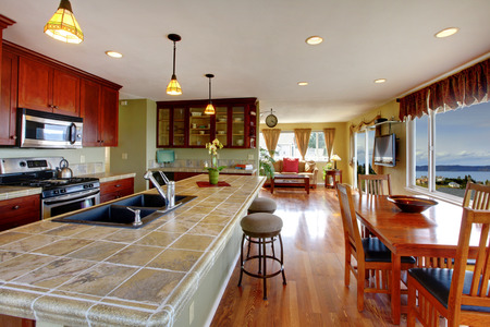 Kitchen room with dining area. View of kitchen island with built-in sink and dining table set photo