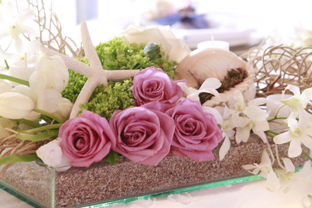 Beautiful wedding decoration made of pink roses blended with sea shell and star, green and white flowers. All perfectly sit in a glass box with sand