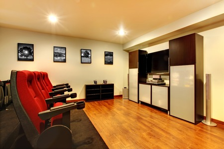 Home TV movie theater entertainment room interior with real cinema chairs.