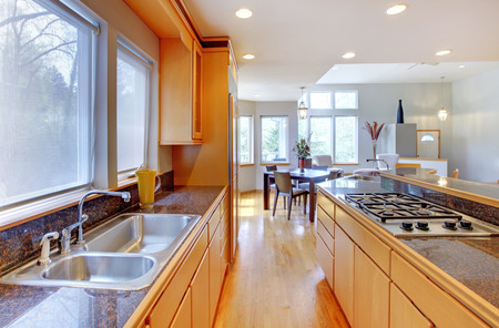 Large luxury modern wood kitchen with granite counter tops and yellow hardwood floor. photo