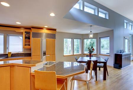 open floor plan: Large luxury modern wood kitchen with granite counter tops and yellow hardwood floor.