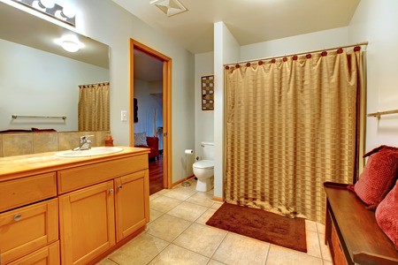 Large bathroom interior with bench with red pillows and shower curtain. Wood cabinet with one sink. photo