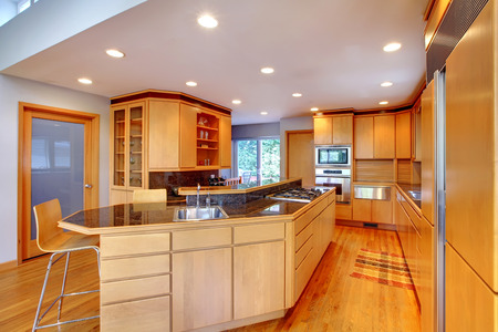 granite kitchen: Large luxury modern wood kitchen with granite counter tops and yellow hardwood floor