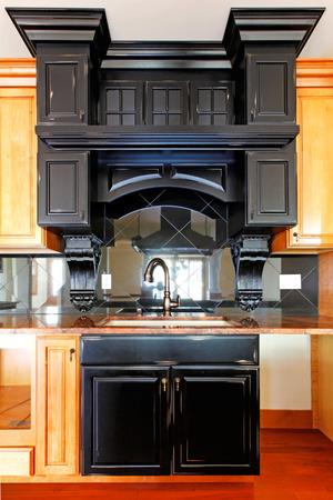 Kitchen island and stove custom wood cabinets  New luxury home interior  photo