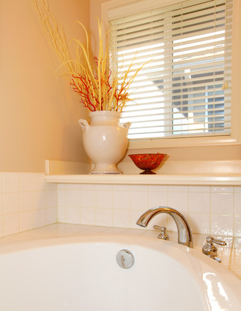 corner tub: White tub  bathroom details with vase and window corner with beige wall