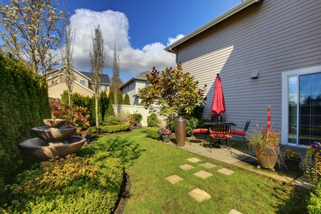 nice house: Spring house back yard with red chairs and umbrella and nice landscape