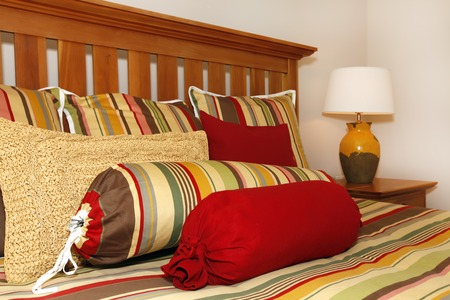 Bed details in red, yellow and green with wood head board
