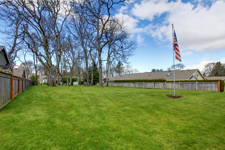 Spacious land area with green lawn, trees and american flag photo