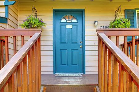 Entree portiek met blauwe deur en trappen met leuningen