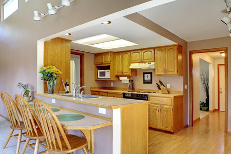 open floor plan: House interior with open floor plan. Kitchen with maple cabinets and bar counter