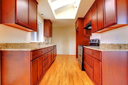 cherry hardwood: Simple kitchen interior with velux windows. VIew of bright cherry cabinets and hardwood floor