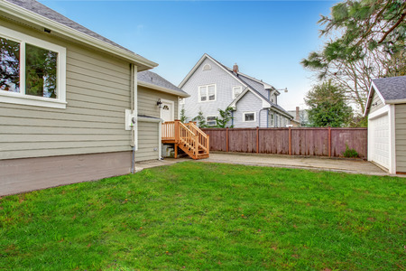 Small house with wooden.deck. Backyard view photo