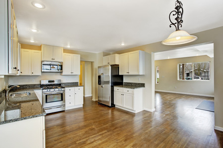 Open floor plan. White kitchen room with steel appliances. View of empty living room