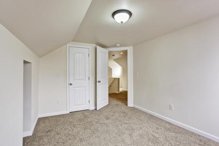 vaulted: Bright empty room with carpet floor and vaulted ceiling. View of hallway through the open door