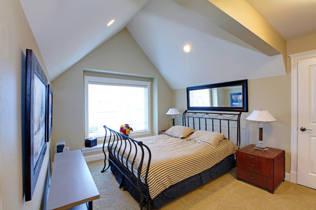 Small bedroom with vaulted ceiling, carpet floor. Furnished with metal frame bed and nightstand, Stock Photo - 28619966