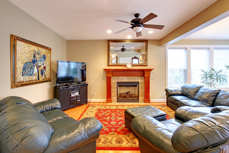 Living room with leather furniture set, tv and fireplace photo