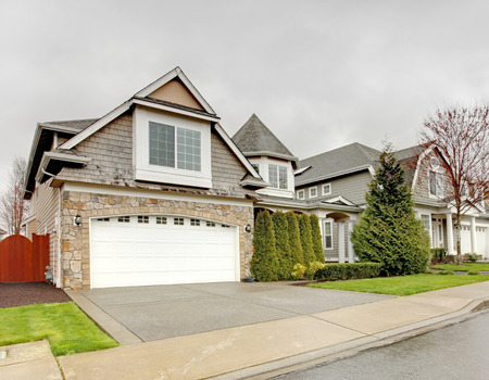 garage door: House esterior. House with stone wall trim, garage, column porch and green lawn.