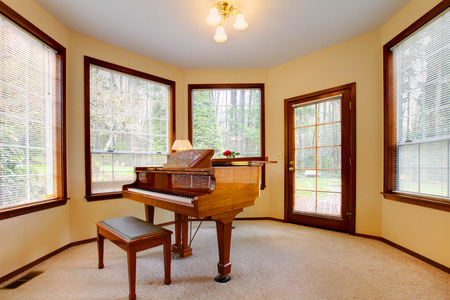 Peaceful room with antique piano and ottaman.