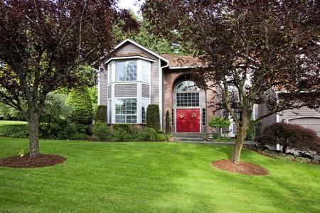 Grande maison de bardage avec voûte en briques haute, porte d'entrée rouge. Banque d'images - 28620230