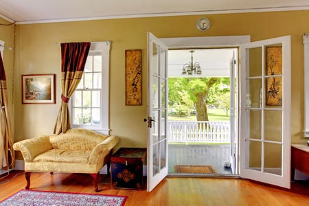 front room: Liviing room with open doors to the front porch. Romantic classic with park view. Stock Photo