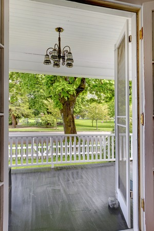 front porch: Open door to the front porch with view of the park and white railing. Stock Photo