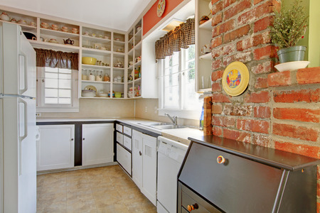 Old simple white kitchen with brick wall. 免版税图像
