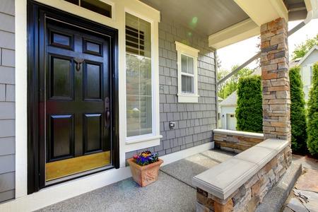 Grijze huis buitenkant met zwarte deur en stenen muur. Stockfoto