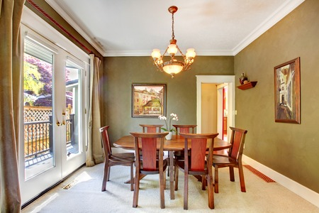 Green classic dining room with art and large door. photo