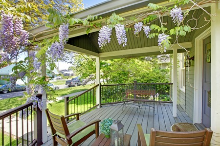 Front house porch with chairs and flowers.