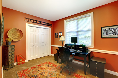 home office: Home office room with bright orange walls and carpet floor furnished with black office furniture