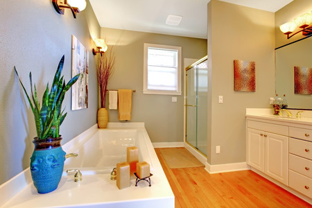 bathroom design: Bathroom interior design with green walls and hardwood floor. View of bath tub decorated with candles and vase