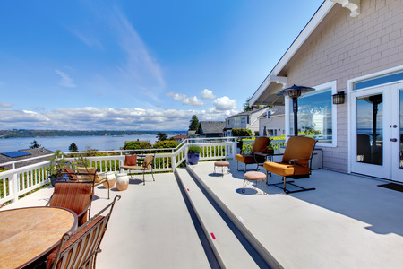 Large white house terrace with water view during summer. photo