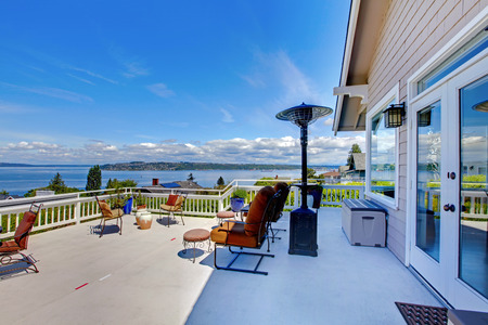 front porch: Large white house terrace with water view during summer.