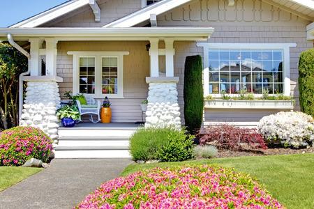 石造りのコラムのトリムと玄関ポーチ。開花茂みと花壇のビュー