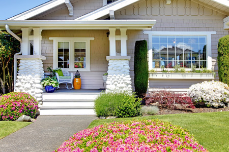 Entrance porch with stone column trim. View of flower bed with blooming bushes Stock Photo - 28688682