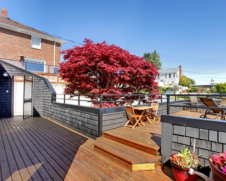 Large outdoor terrace with furniture in the front of the house  photo