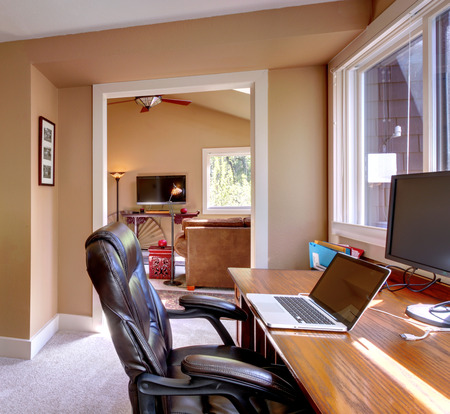 home furniture: Home office and computer and chair with brown walls and TV in living room