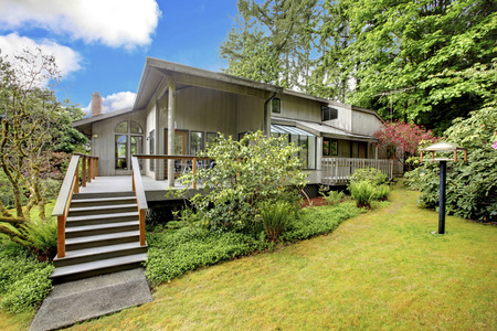 Large house with entrance porch and deck  View of front yard with green lawn and bushes photo