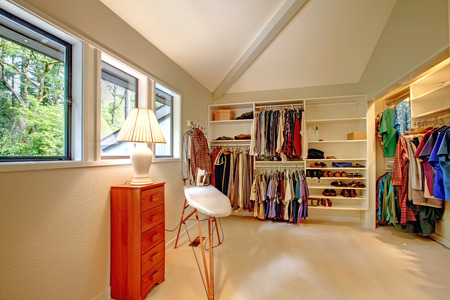 Spacious walk-in closet with built-in shelves  Closet full of cloths, shoes  View of ironing board and small cabinet