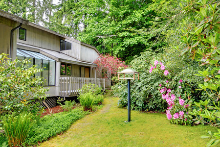 screened: Green front yard with blooming bushes and flower bed  View of walkout deck and screened porch Stock Photo