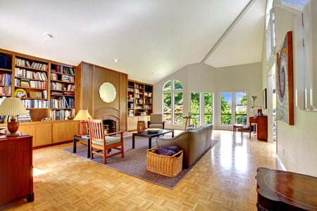 Large room with high vaulted ceiling, home library, fireplace, leather couch photo