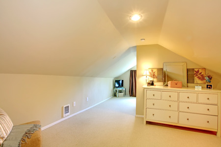 Long TV attic room with white furniture and beige colors. Imagens