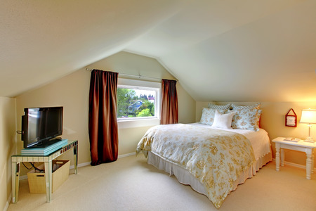 attic: Beige attic bedroom with TV, brown curtains and white bed.