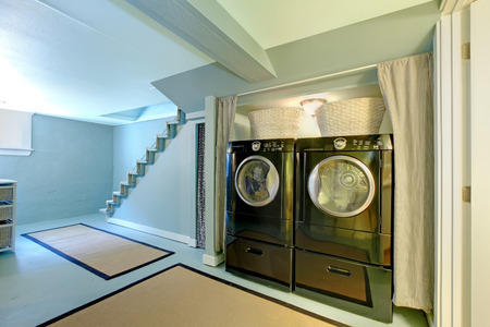 Blue basement laundry room with black washe and dryer. photo